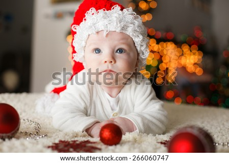 Baby is playing with christmas ornaments for the first time - stock photo