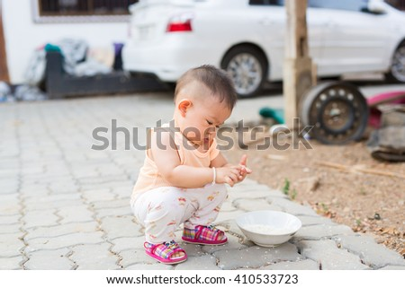 baby is sitting in squat position during playing something. - stock photo