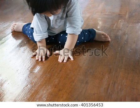 Baby is sitting on the wood floor, play and learn time - stock photo