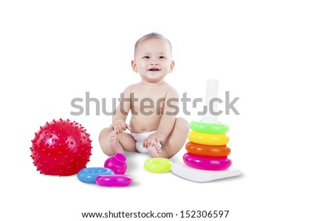 Baby is sitting with toys on white background - stock photo