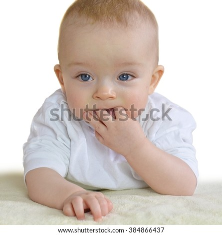 Baby is sucking fingers because of his first teeth. - stock photo