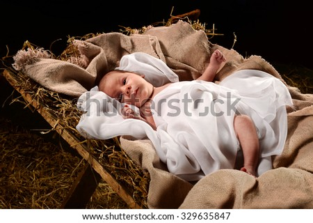 Baby Jesus when born on a manger wrapped in swaddling clothes over dark background - stock photo