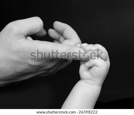 Baby keeps for a daddy's finger - stock photo