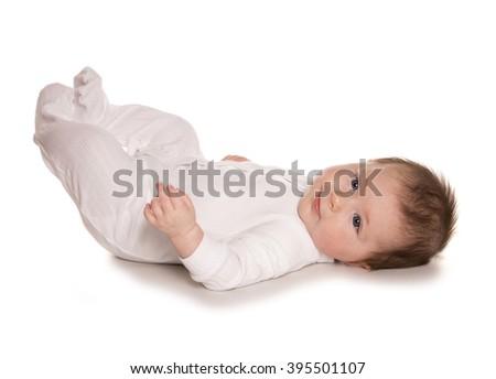 Baby kicking feet white background - stock photo