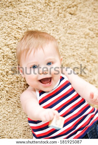 Baby: Laughing Baby Laying On Rug - stock photo