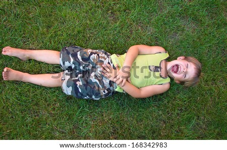 Baby laughing, lying on the grass - stock photo