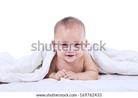 Baby laughing under blanket inside the house. isolated on white - stock photo