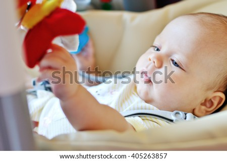 baby laying in bouncer chair and playing toy - stock photo