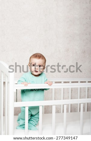 baby learns to stand on his feet . friendly smiling child - stock photo