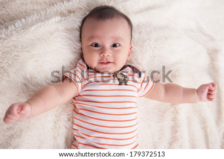 baby lies on his back and smiling while looking at the camera - stock photo