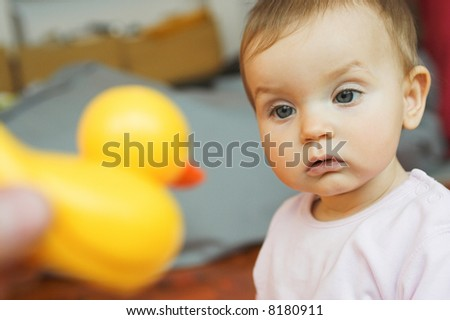 baby looking at plastic duck toy; confused - stock photo