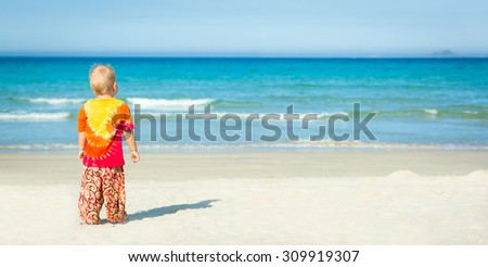 Baby looking sea on the beach. Panorama - stock photo