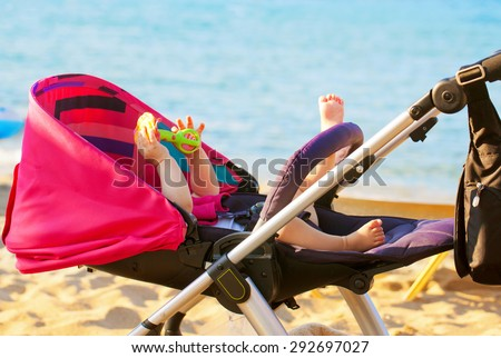 Baby lying in a stroller on the beach. Family holiday - stock photo