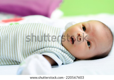 Baby lying on a bed while looking around: he want to talk with you - stock photo