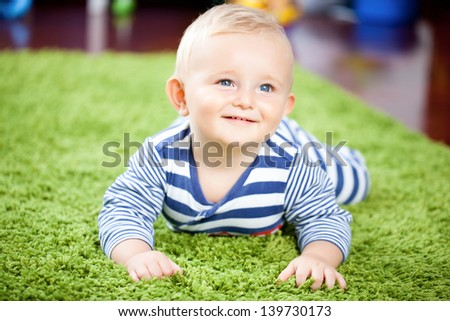 Baby lying on a green carpet - stock photo