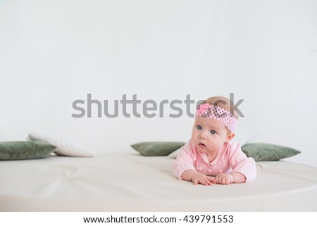 baby lying on his stomach on the floor and looking forward. Beautiful baby girl in pink. - stock photo