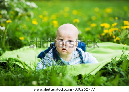 Baby lying on the grass in the park - stock photo