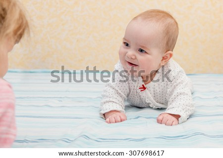 Baby lying on tummy and elbows and looking admiringly at sibling. Selective focus on the baby. Older child is at the frame edge, unfocused.  - stock photo
