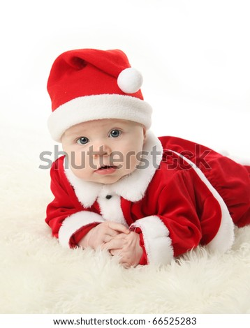 Baby lying on tummy wearing a red and white Christmas Santa hat and suit, isolated on a white background. - stock photo