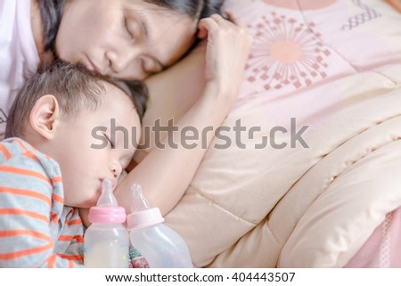 Baby milk bottle and water bottle holdind by asian baby boy. Asian baby boy sleeping in mother arm  - stock photo