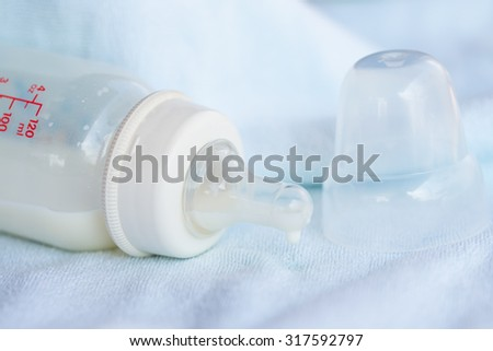 Baby milk bottle with milk drop on the towel - stock photo
