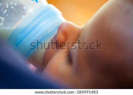 Baby new born close up whit bottle of milk - stock photo