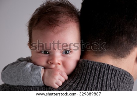 Baby newborn lying on parents shoulder, open eyes, baby boy sucking fingers, father - stock photo