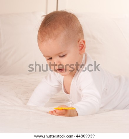 Baby on a bed playing with plastic yellow toy - stock photo
