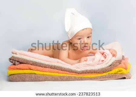 baby on colorful towels stack - stock photo