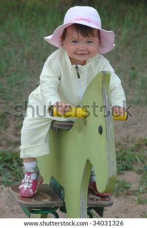 Baby on the wooden toy - stock photo