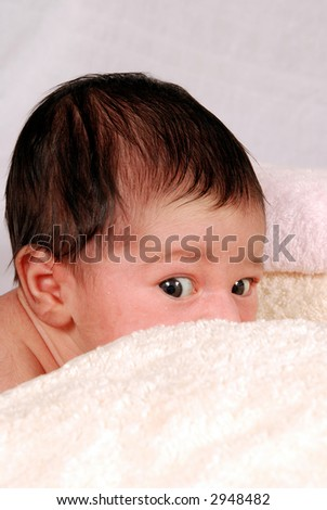 baby peeking behind towels - stock photo