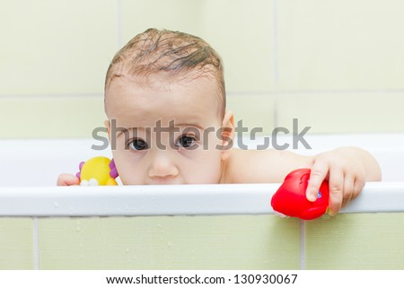 Baby peeking out of the tub while bathing. - stock photo