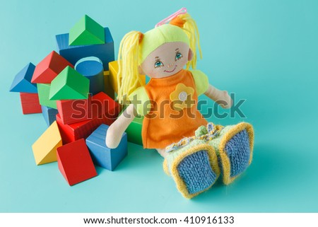 Baby play  concept, cloth doll and wooden bilding blocks for play - stock photo