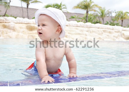 Baby playing and splashing in a tropical resort pool - stock photo