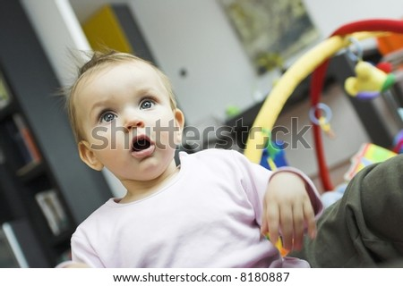 baby playing in a bedroom - looking suprised - stock photo