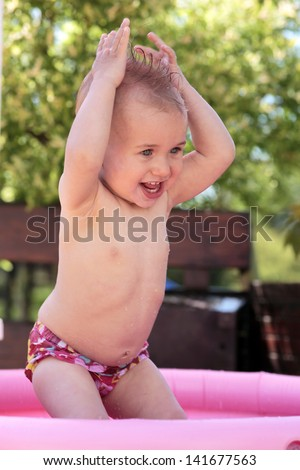 Baby playing in water in kiddie pool - stock photo