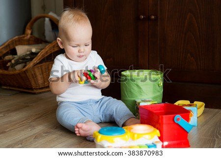 Baby playing with colorful toys at home interior - stock photo