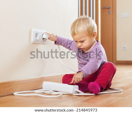 Baby playing with electrical extension on floor at home - stock photo