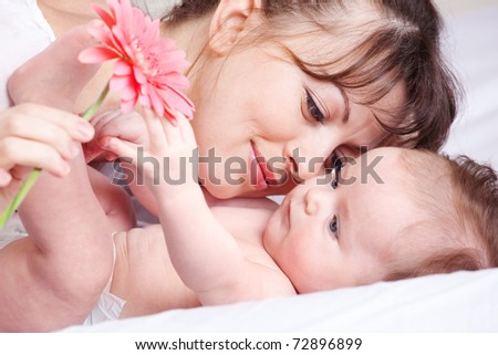 Baby playing with flower - stock photo