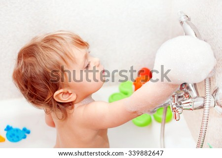 Baby playing with foam and water tap in the bathroom - stock photo