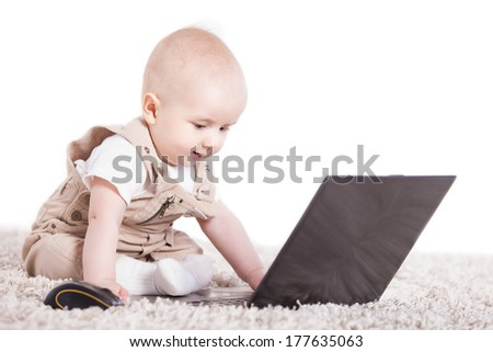 Baby playing with laptop on the white background - stock photo