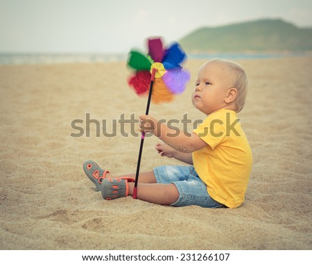 Baby playing with toy windmill - stock photo