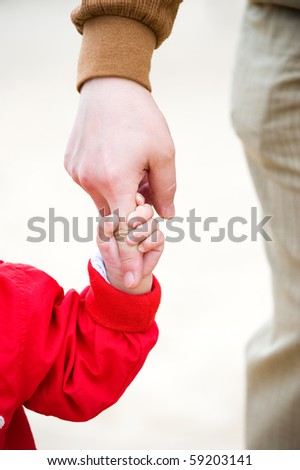 Baby reaching up to hold on to father's finger. - stock photo