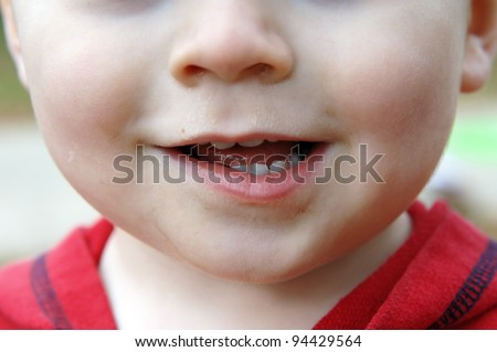 Baby's face is dirty and he is giving a lop-sided grin.  Baby teeth show in his mouth. - stock photo