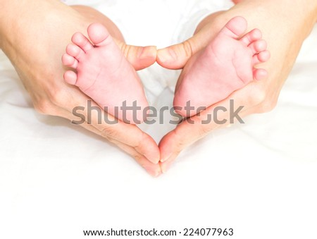 Baby's feet in mother's hand - stock photo