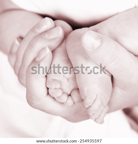 Baby's feet on mommys hand - stock photo