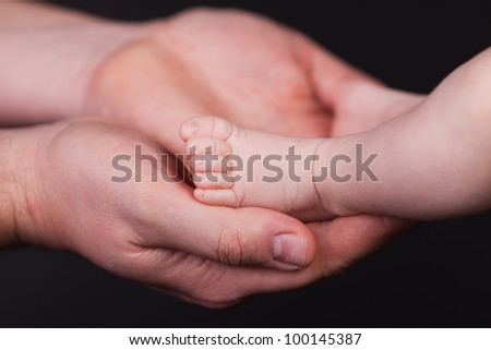 Baby's foot in father hands. - stock photo