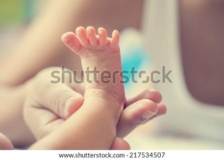 Baby's foot in mother hands - stock photo