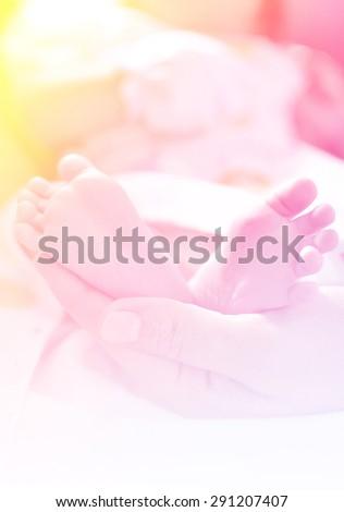 Baby's foot in mother hands. - stock photo