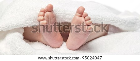 baby's foot under towel closeup isolated on white - stock photo